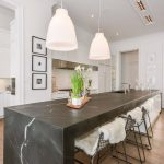 Open-space-kitchen-with-black-marble-waterfall-island